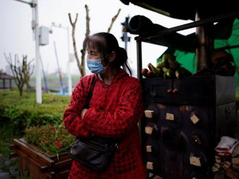 Li Yu, de 55 años, vendedora de maíz, usa una mascarilla en la antigua muralla de la ciudad de Jingzhou después de su reapertura el 26 de marzo de 2020.