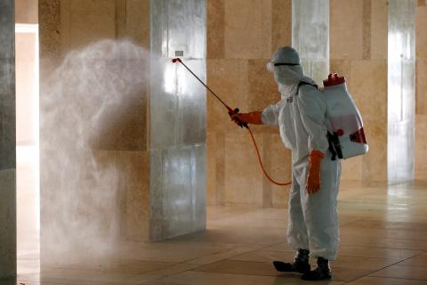 Operario desinfecta un edificio por el coronavirus