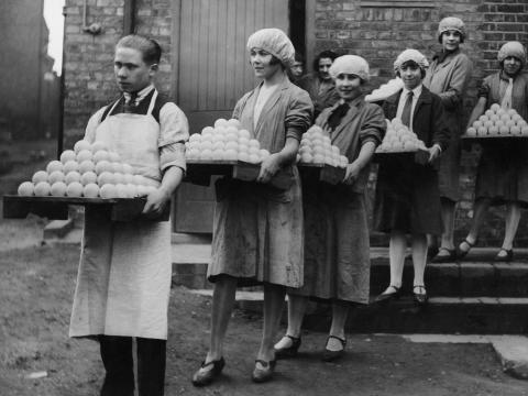 Las trabajadoras cargan pelotas de tenis recién fabricadas.