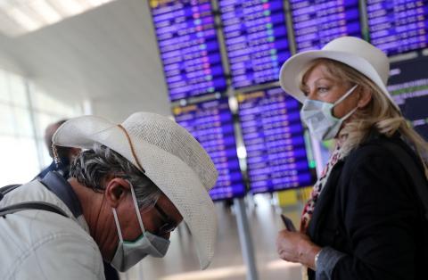 Una pareja de turistas se cubren con mascarillas por la crisis del coronavirus.