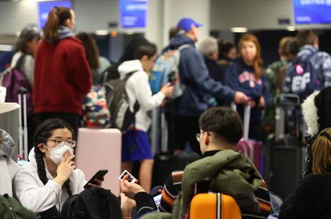 Pasajeros con mascarillas por el coronavirus en un aeropuerto.