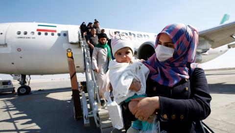 Pasajeros con mascarillas protectoras descienden de un avión en el aeropuerto de Najaf (Irán)