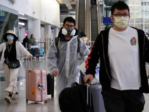 Un pasajero que regresa de Londres lleva un traje protector en el aeropuerto internacional de Hong Kong, el 17 de marzo de 2020.