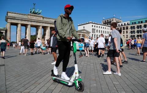 Un hombre conduce un patinete eléctrico compartido enfrente de la Puerta de Brandemburgo, en Berlín, Alemania.
