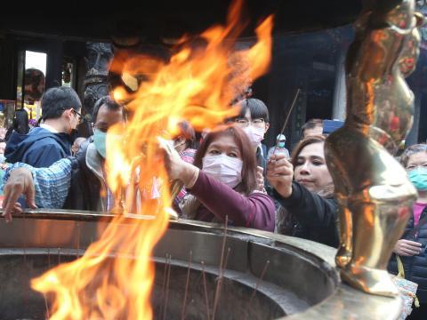 La gente reza en el popular Templo Longshan en Taipei el jueves.
