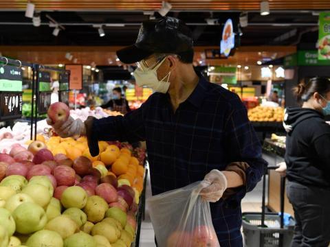 Un hombre con mascarilla y gafas coge manzanas dentro de un supermercado en Wuhan, provincia de Hubei, el 26 de marzo de 2020.