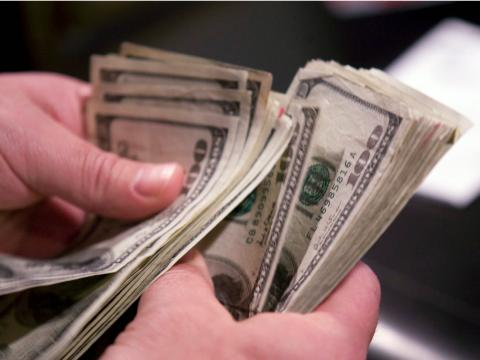 Persona cuenta billetes de 100 dólares.