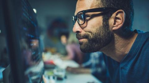 Una persona junto a un monitor de ordenador.