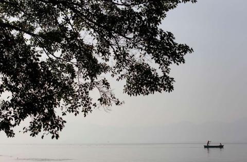 Un pescador local navega en su bote para cruzar el Lago de Ilopango, en las afueras de San Salvador.