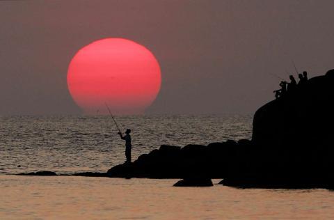 Un pescador tailandés pesca durante la puesta de sol, cerca de la playa Patong, en la isla de Phuket.
