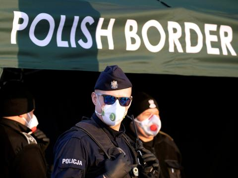 A Polish police officer, wearing a protective mask, stands at the border between Germany and Poland on March 23, during coronavirus disease symptoms testing for people returning to Poland.