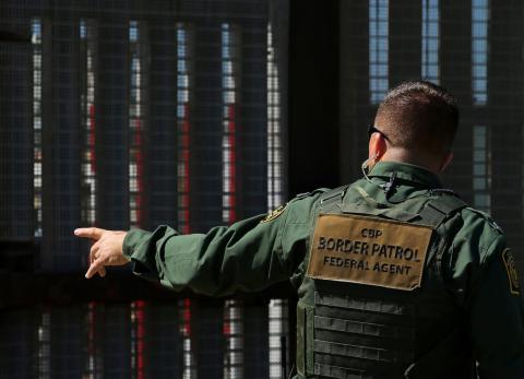 Un policía fronterizo estadounidense junto a la valla con México.