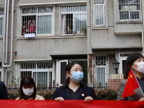Los residentes despiden desde sus casas a un equipo médico de la provincia de Guizhou que sale de Wuhan, China, el 25 de marzo de 2020.