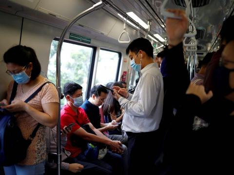 Commuters wearing masks in precaution of the coronavirus outbreak are pictured in a train during their morning commute in Singapore February 18, 2020.