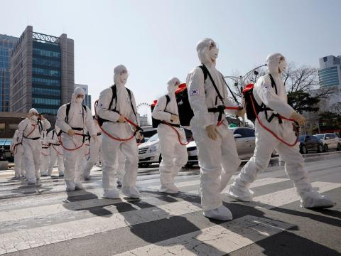 South Korean soldiers wearing protective gear walk on a street in front of Daegu's city hall after the rapid rise in confirmed cases of the coronavirus on March 2, 2020.