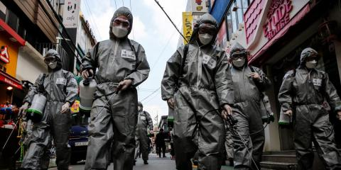 South Korean soldiers in protective gear sanitizing a shopping street in Seoul, South Korea, on Wednesday.