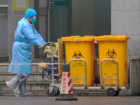 A staff member moves bio-waste containers past the entrance of the Wuhan Medical Treatment Center in Wuhan, China, where some people infected with the new virus are being treated on January 22, 2020.