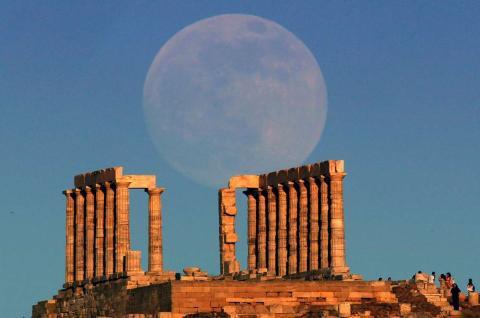La súper luna se eleva sobre el templo de Poseidón, el dios griego de los mares, en Cabo Sunion, Grecia.