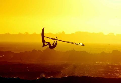 Un surfista hace una acrobacia durante la puesta de sol, en la playa de Blaauwberg, en la Ciudad del Cabo.