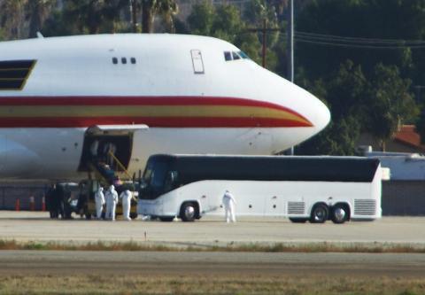 Los trabajadores de la salud se encuentran con evacuados de Wuhan, China, en la Base de la Reserva Aérea March en Riverside, California, el 29 de enero de 2020.