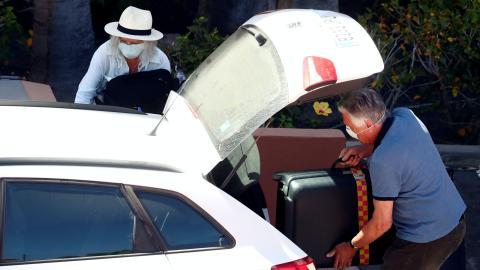 Un taxista recoge a unos clientes con mascarilla por el coronavirus.