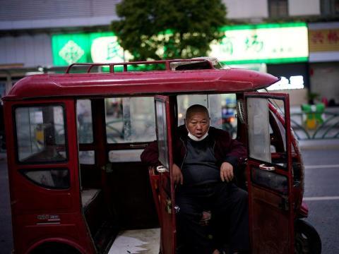 Un hombre con una mascarilla se sienta en su vehículo mientras espera clientes en Xianning, el 25 de marzo de 2020.