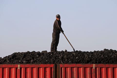 Un trabajador carga carbón en un camión cerca de una mina del grupo estatal Longmay en las afueras de Jixi, Heilongjiang, China
