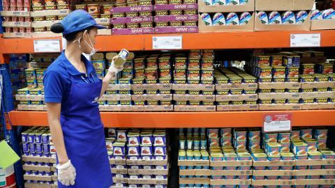 Una trabajadora mira latas de Spam en un supermercado de Filipinas.