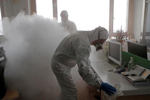 Trabajadores desinfectando un puesto de trabajo en una oficina.