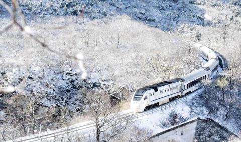 Un tren viaja a través de colinas cubiertas de nieve en las afueras de Beijing, China.