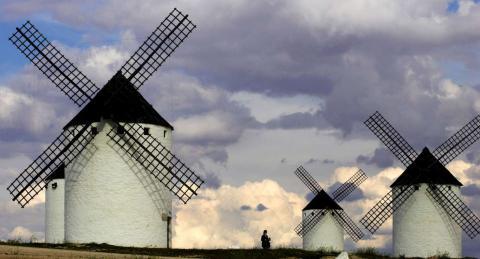 Los turistas visitan los antiguos y famosos molinos de viento en el centro de España.