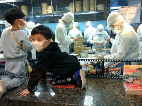 Dos niños observan cómo los chefs hacen dumplings en Taipei el sábado.