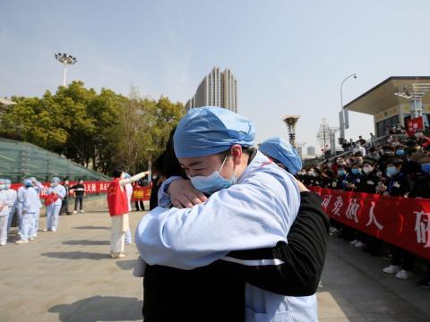 Un trabajador sanitario local se abraza y se despide de un médico de Jiangsu en la estación de tren de Wuhan el 19 de marzo de 2020.