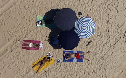 Varias personas toman el sol en una playa de Portugal