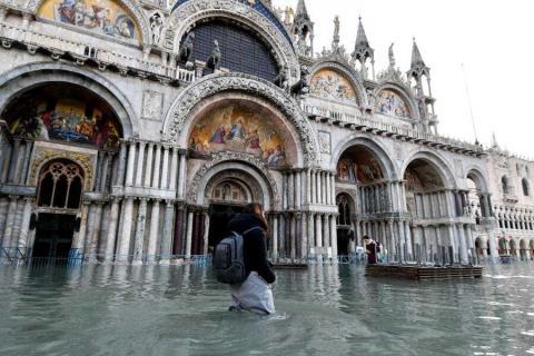 Una mujer caminando a través del agua durante una marea alta en la Plaza de San Marcos, Venecia, e 23 de diciembre de 2019.
