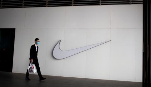 Un viandante con mascarilla pasa ante la tienda Nike de Pekín (China)