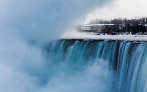 El viejo edificio de una hidroeléctrica se ve detrás de las Cataratas del Niagara, con temperaturas bajo cero, en Ontario.
