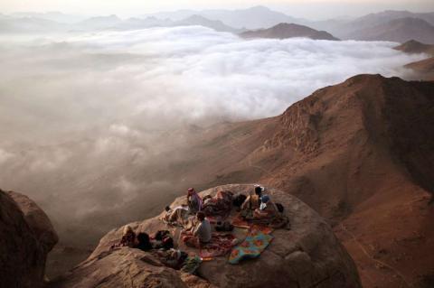 Los visitantes observan la salida del sol desde el Monte Moisés, en la península Sinaí.