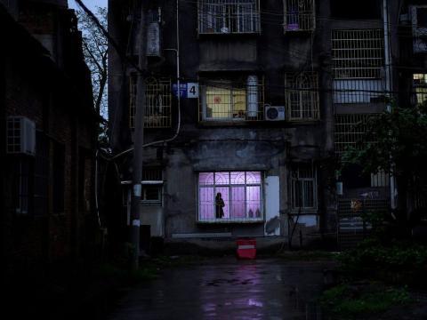 Un hombre se para frente a una ventana en una comunidad residencial en Jingzhou, el 26 de marzo de 2020.