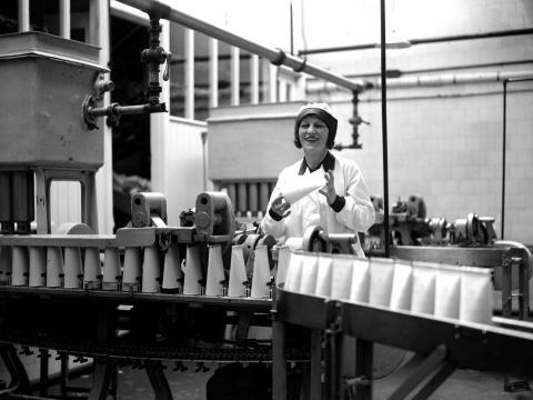 Una mujer en una planta de embotellado de leche en la década de 1920.