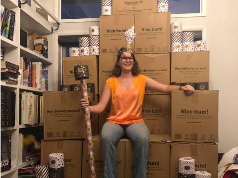 """A woman sits on top of a """"throne"""" made of boxes containing toilet paper in Toowoomba, Australia, on March 5, 2020."""