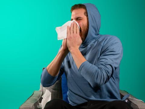 Hombe estornudando