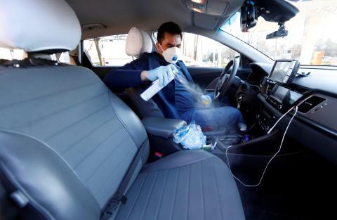 Un taxista desinfectando su taxi.