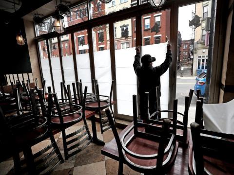 Un empleado de Carmelina's en el North End de Boston pega papel en las ventanas del restaurante que está temporalmente cerrado durante la pandemia de coronavirus, 25 de marzo de 2020.