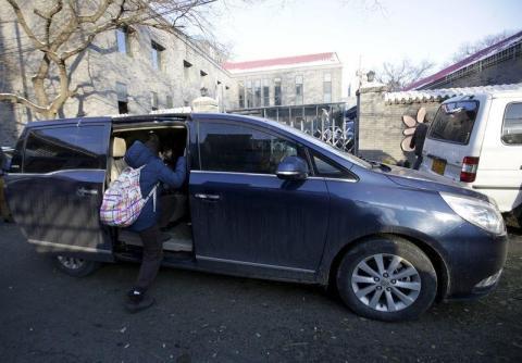 Una estudiante de primaria se sube a una minivan mientras su madre la recoge del colegio, en Pekín.