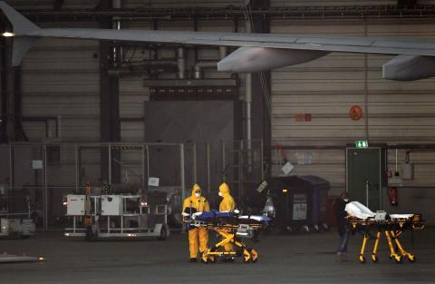 """El personal médico espera a los pacientes con coronavirus de Bérgamo que llegan al aeropuerto de Hamburgo, mediante el Airbus A310 """"Medevac"""" el 29 de marzo."""