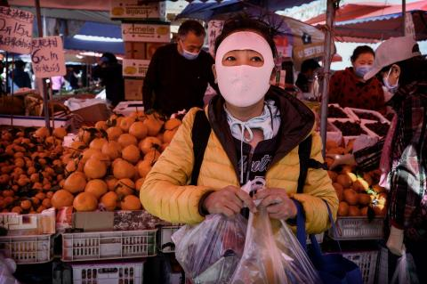 Una mujer china utiliza una máscara protectora que cubre todo su rostro mientras compra en un mercado al aire libre en Pekín, China, el 3 de abril de 2020.