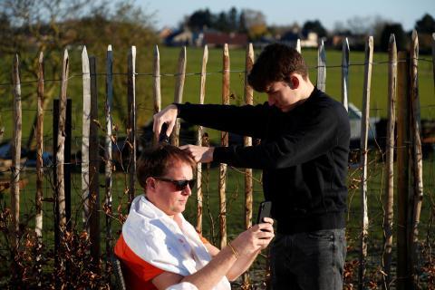 Un adolescente corta el pelo a su padre en su casa, durante el confinamiento impuesto por el gobierno belga, en Moorsel, (Bélgica), el 31 de marzo de 2020.