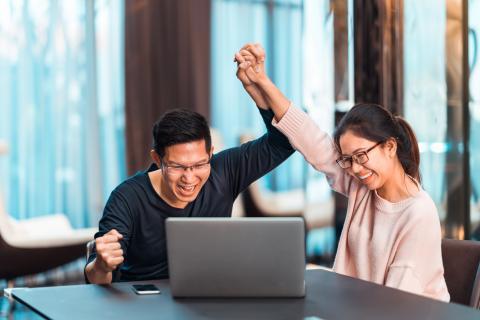 Dos personas celebrando frente a un ordenador