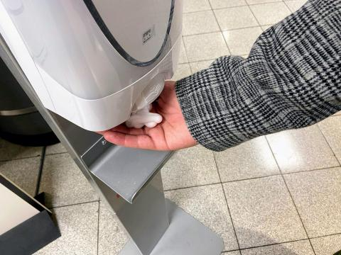 A person reaching for hand sanitizer.